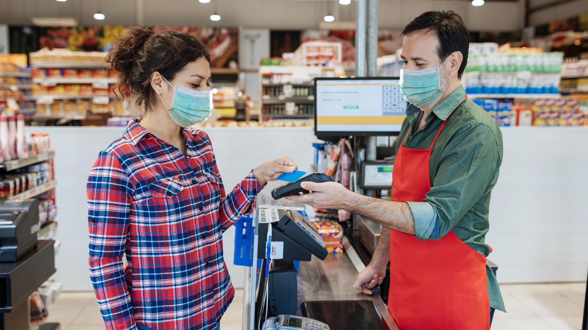 Supermarket cashier and buyer with face masks