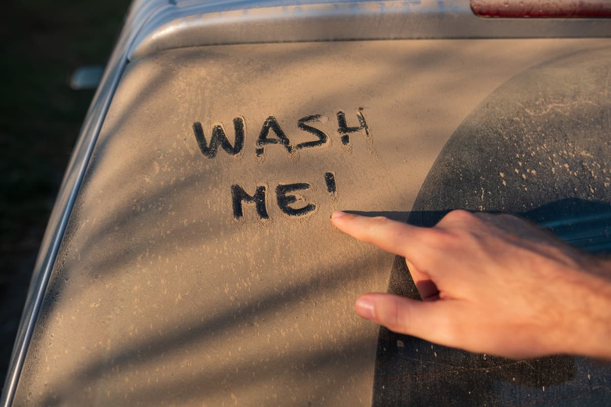 A dirty car with someone writing